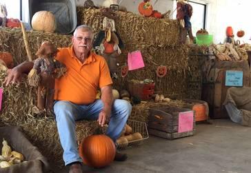 Pumpkin Bob Kautz sitting on a hay bale